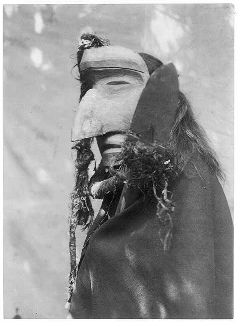 Person-wearing-ceremonial-mask-of-the-Nuhlimahla-during-the-during-the-Winter-Dance-ceremony.-These-characters-impersonated-fools-and-were-noted-for-their-devotion-to-filth-and-disorder