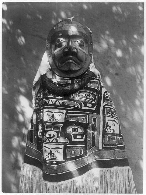Woman-wearing-a-fringed-Chilkat-blanket-a-hamatsa-neckring-and-mask-representing-deceased-relative-who-had-been-a-shaman